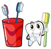 A tooth holding a toothbrush beside the glass Stock Image