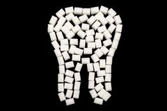 White tooth made of sugar cubes against a black background royalty free stock photo