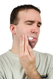 Tooth Pain. A man suffering from a toothache and holding some cotton in his mouth to help, isolated against a white background Stock Photo