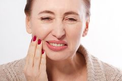 Tooth pain and dentistry. Macro face of middle age woman suffering about strong teeth pain, touching cheek by hand isolated on whi. Te. Painful toothache. Dental Stock Photos
