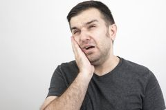 Tooth Pain. Young man at tooth ache on white stock photos