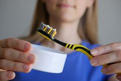 Tooth powder for teeth whitening on the toothbrush in the hands of the girl. A young woman with blond hair holds funds for oral royalty free stock image