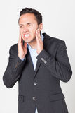 Toothache. Businessman having toothache on bright background stock photos