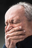 Toothache.  Elderly man with face closed by hand Stock Image
