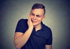 toothache Frustrierter junger Mann in den Schmerz, die seine Backe berühren lizenzfreies stockbild
