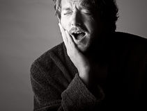 Toothache. Ouch!. Dramatic Black and White Shot of a Man in Pain holding his Jaw. Toothache stock photography