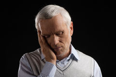Toothache. Portrait of white hair senior man holding his hand on cheek while isolated on black Royalty Free Stock Photo