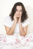 Toothache woman. Young woman having toothache sitting on bed isolated on white background stock image