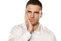 Toothache. A young man with a toothache on white background Stock Photo