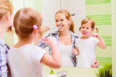 愉快的家庭母亲和掠过她的牙toothb的女儿孩子 免版税库存照片