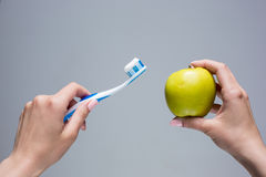 Toothbrush and apple in woman's hands on gray Stock Photo