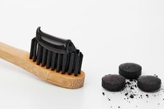 Toothbrush with black charcoal toothpaste. Black toothpaste on toothbrush with activated charcoal pills stock image