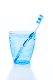 Toothbrush in blue plastic glass Stock Photography