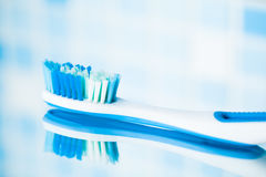 Toothbrush on blue tile background with mirror reflection Stock Photography