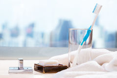 Toothbrush in a clear glass on bathroom countertop with soap and Royalty Free Stock Photo