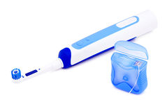 Toothbrush and dental floss. Electric toothbrush and inter-dental floss on a white background Royalty Free Stock Images