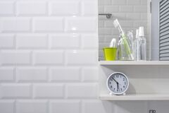 Toothbrush in glass bottle, tooth paste in little green bucket, hand sanitizer spray with clock on shelf and mirror on white tiles