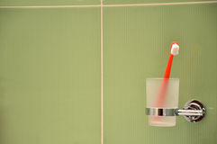 Toothbrush in glass in metal holder fixed to green tile at wall in bathroom Stock Images