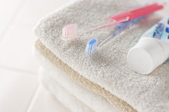 Toothbrush, glass and towels on white tile Stock Images