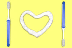 Toothbrush and heart shaped toothpaste. Concept for Healthy Dental Campaign. We love to brush our teeth. Isolate on yellow background stock images