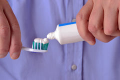 Toothbrush paste. Pouring toothpaste on toothbrush on white background.Toothpaste being squeezed onto toothbrush Stock Image
