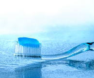 Toothbrush with paste on wet glass. Toothbrush with paste on glass with water splashes, backlight Royalty Free Stock Photography