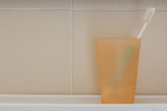 Toothbrush in plastic glass. The used toothbrush in orange plastic glass with dirty background Stock Image