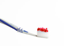 Toothbrush with red colored sugar. Isolated toothbrush with red colored sugar on it in front of white background Royalty Free Stock Images