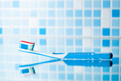 Toothbrush with red stripe toothpaste and mirror reflection Royalty Free Stock Image