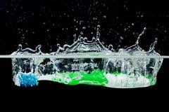 Toothbrush with splashing water Royalty Free Stock Image