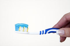 Toothbrush with toothpaste. Womans hand holding toothbrush with toothpaste Royalty Free Stock Photography