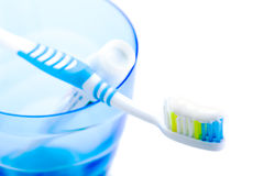 Toothbrush and toothpaste in blue plastic glass Royalty Free Stock Photography