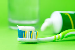 Toothbrush and toothpaste. Close up of toothbrush and toothpaste tube on green background Royalty Free Stock Images