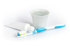 Toothbrush, toothpaste and a cup of water. Blue toothbrush, toothpaste and a cup of water stock images