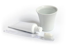 Toothbrush, toothpaste and a cup of water. Stock Photography