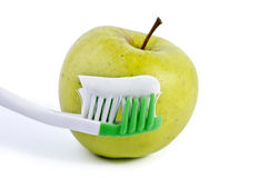 Toothbrush with toothpaste and green apple isolated over white Royalty Free Stock Photos