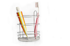 Toothbrush beside toothpaste in metal holder Stock Photography