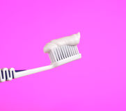 Toothbrush with Toothpaste on Pink Background Royalty Free Stock Images