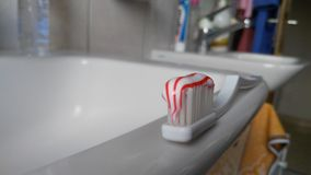 Toothbrush with toothpaste on a sink Stock Photo