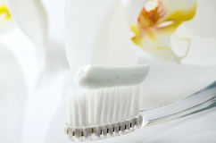 Toothbrush with toothpaste on a white table against the backgrou Royalty Free Stock Image