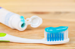 Toothbrush and Toothpaste. Toothbrush and Toothpaste on a wooden background Royalty Free Stock Photo