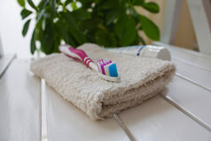 Toothbrush and towels. Toothbrush on a white towel, against greens Stock Image