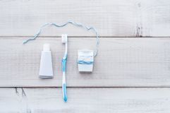 Toothbrush, toothpaste and dental floss on a weathered wood back. Toothbrush, tube of toothpaste and dental floss on a weathered wood background stock photography