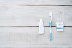 Toothbrush, toothpaste and dental floss on a weathered wood back stock photo