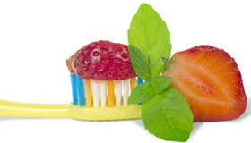 Toothbrush. Yellow toothbrush with mint green and red strawberries, isolated on white background Stock Images