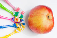 Toothbrushes and apple Stock Photos