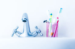 Toothbrushes on basin near water tap Royalty Free Stock Image