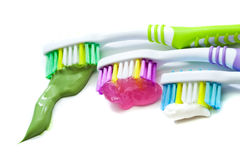 Toothbrushes closeup. Three multi-colored toothbrushes with toothpaste closeup on white background Royalty Free Stock Photography