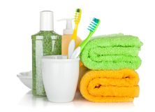 Toothbrushes, cosmetics bottles and two towels Stock Images