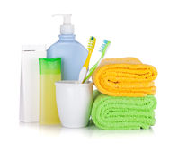Toothbrushes, cosmetics bottles and two towels Royalty Free Stock Photos